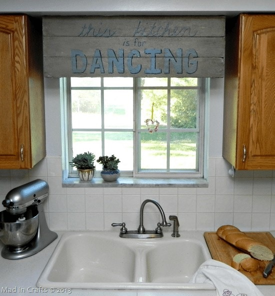 A rustic sign above a kitchen sink that reads