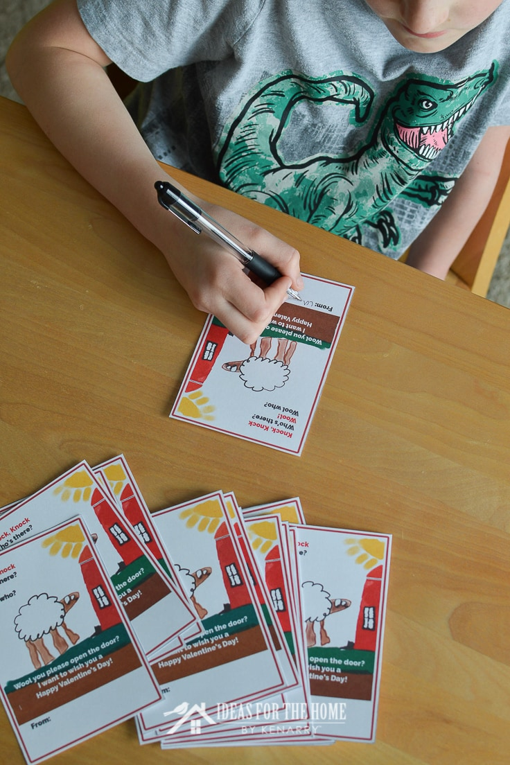 Boy signing his name on a Valentine's Day card