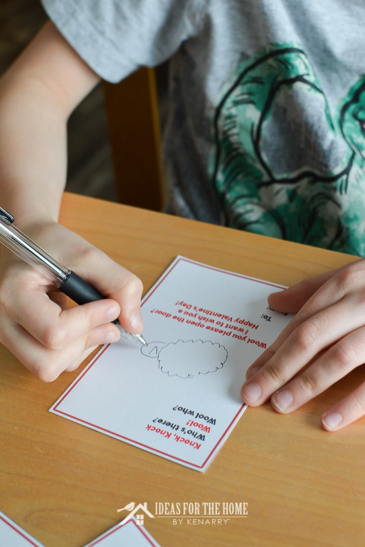 Boy drawing a sheep on a Valentine's Day card for friends at school