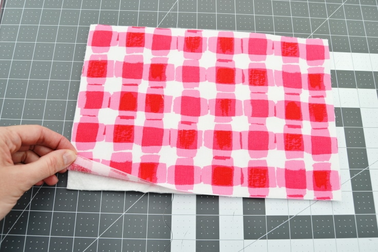 first step of how to sew a hot pad tutorial- making a stack with one of the pieces of batting laid down with one of the woven cotton fabric pieces on top with the right side up