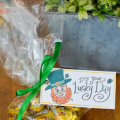 Leprechaun printable gift tag attached to the top of a cellophane bag filled with chocolates covered in gold foil