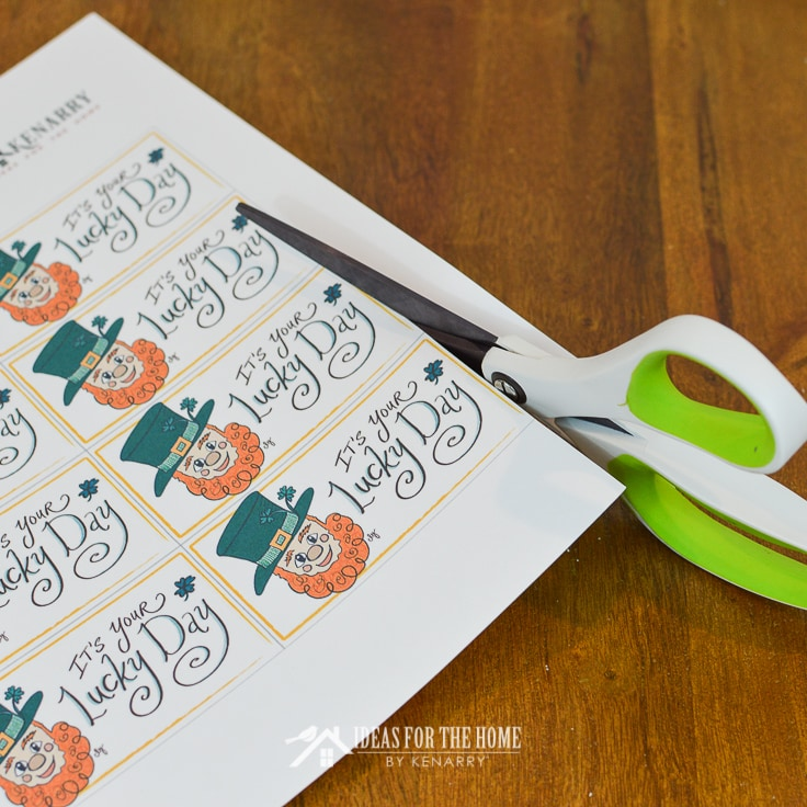 Scissors cutting apart gift tags for St. Patrick's Day