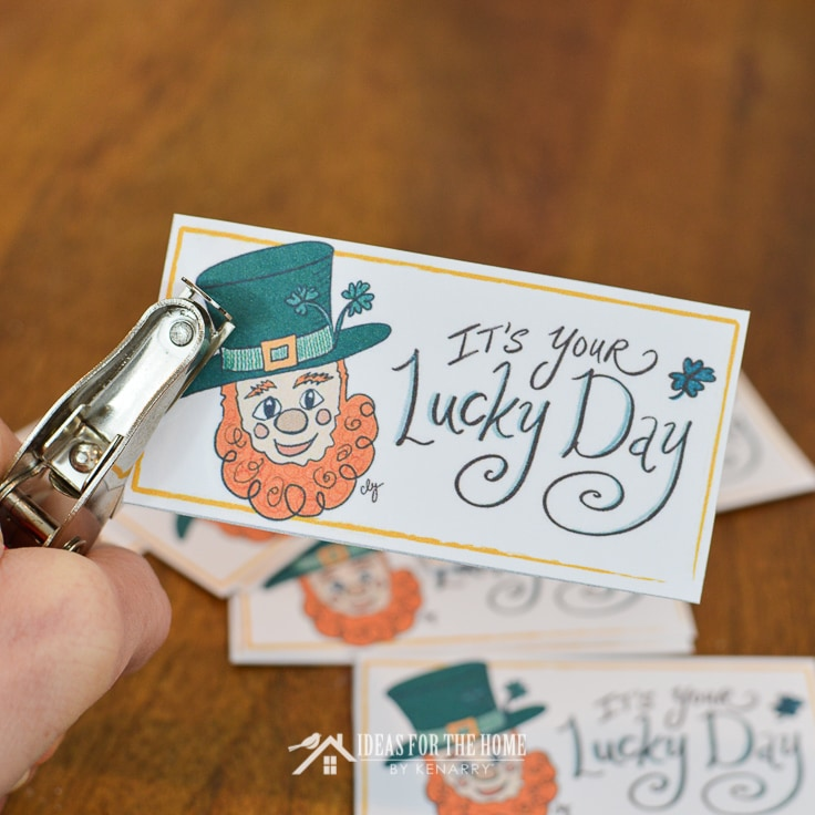 Close up of a hole punch putting a hole in the side of a gift tags for St. Patrick's Day that says