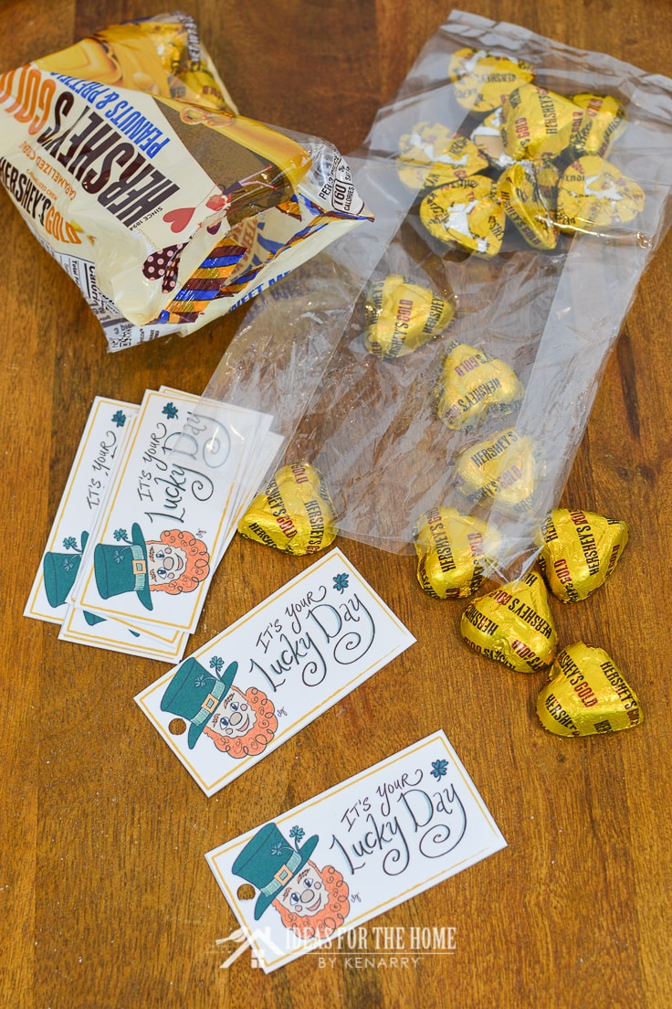 Chocolate candy wrapped in gold foil being put into a treat bag for St. Patrick's Day with free printable gift tags