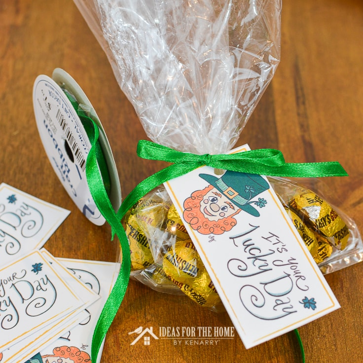 Green satin ribbon being tied around the top of a treat bag for St. Patrick's Day