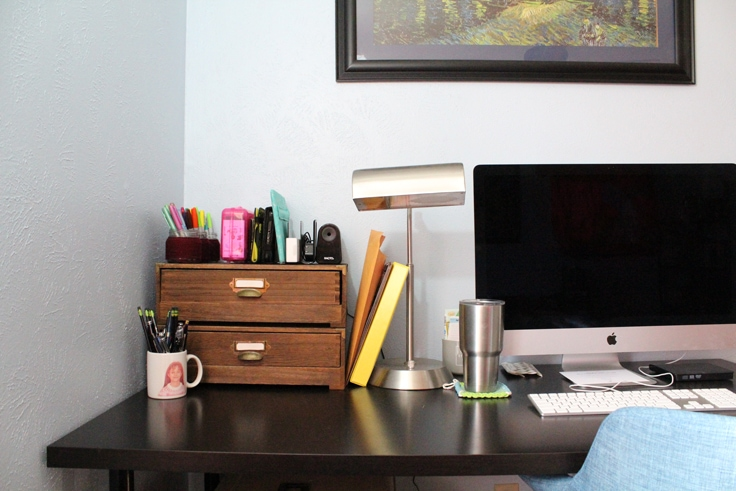 black desk with an iMac, a lamp, and 2 drawers stacked with planner supplies