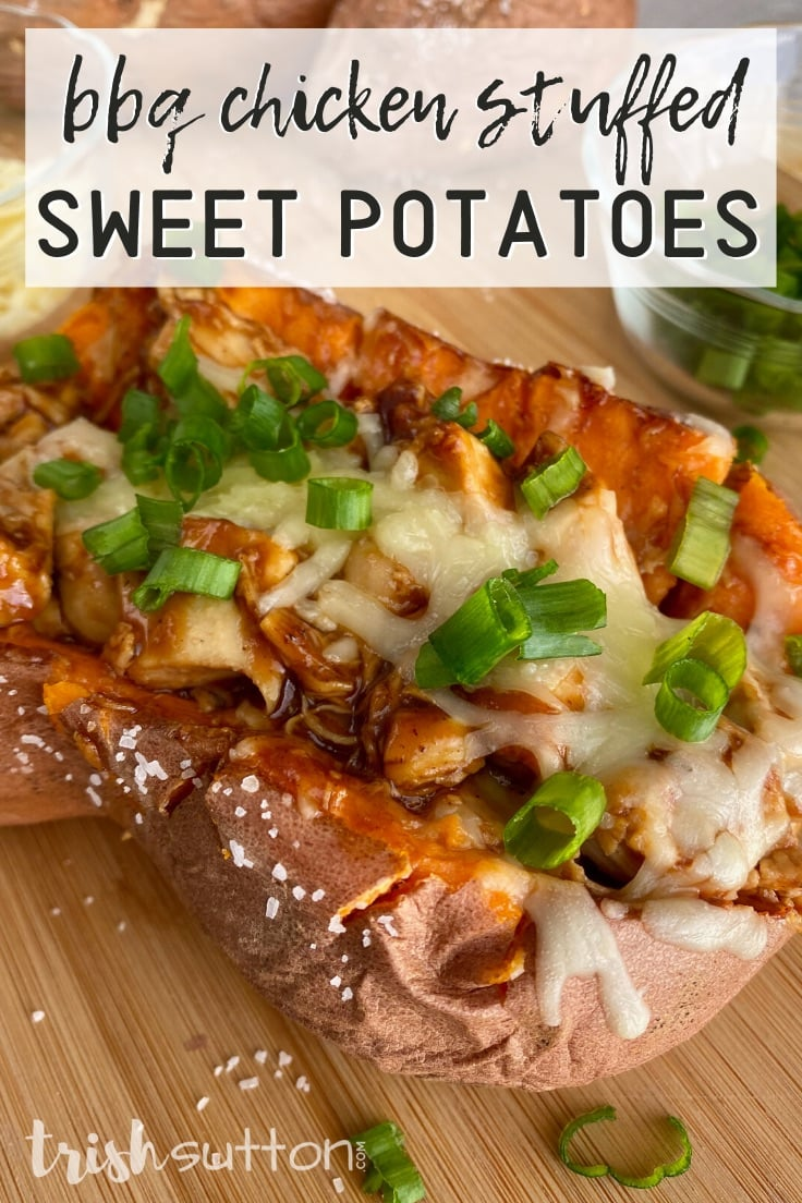 Baked sweet potato stuffed with chicken topped with cheese & green onions on a cutting board.