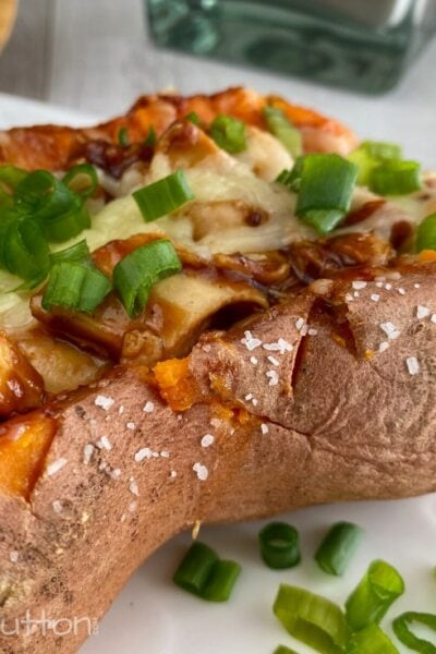 Baked sweet potato stuffed with chicken topped with cheese & green onions on a white plate.