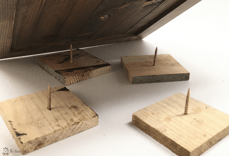 4 small square boards with screws in them that make a painter's pyramid.