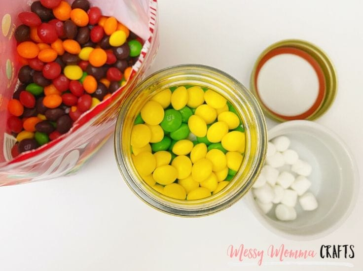 Layer the Skittles in the mason jars to create a rainbow.