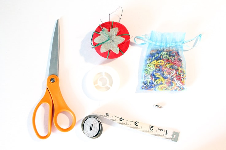 craft supplies including scissors, a soft tape measure, white jewelry thread, a tomato pincushion with sewing needles, and a bag of assorted seed beads
