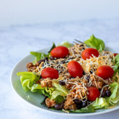 A plate filled with a fresh taco salad made of lettuce, crushed nacho chips, ground taco meat, tomatoes, black beans and cheese