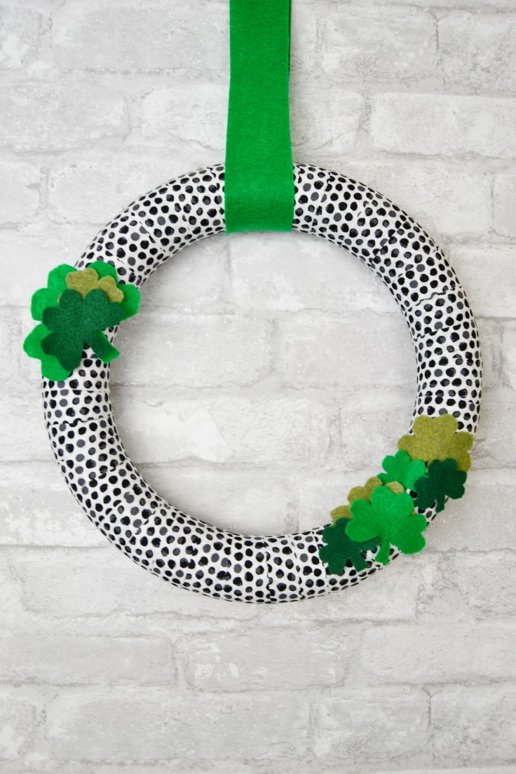 DIY St. Patrick's Day Wreath hanging on a brick wall