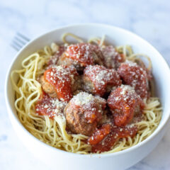 A bowl of freshly prepared spaghetti topped with homemade meatballs smothered in tomato sauce and sprinkled with parmesan cheese