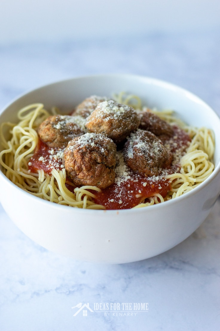 Homemade meatballs topped with parmesan cheese in a bowl full of spaghetti