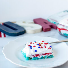 A colorful slice of cake made with jello and angel food cake in red, white and blue layers