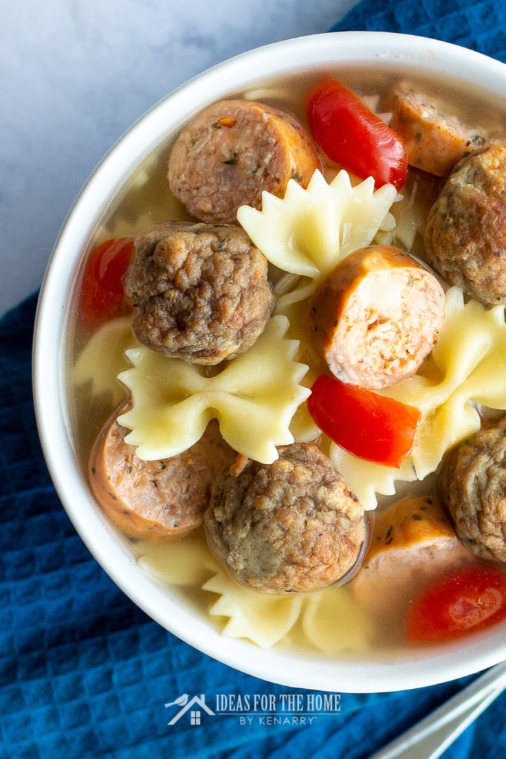 Close up of homemade meatballs, smoked turkey sausage and bow tie pasta with vegetables in a soup