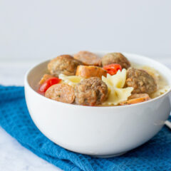 A bowl of meatball and sausage soup with pasta