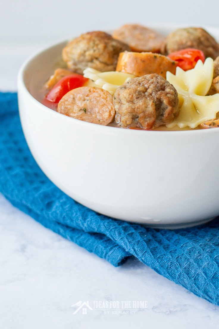 Close up of a soup bowl filled with chicken broth, sausage, pasta, meatballs and vegetables