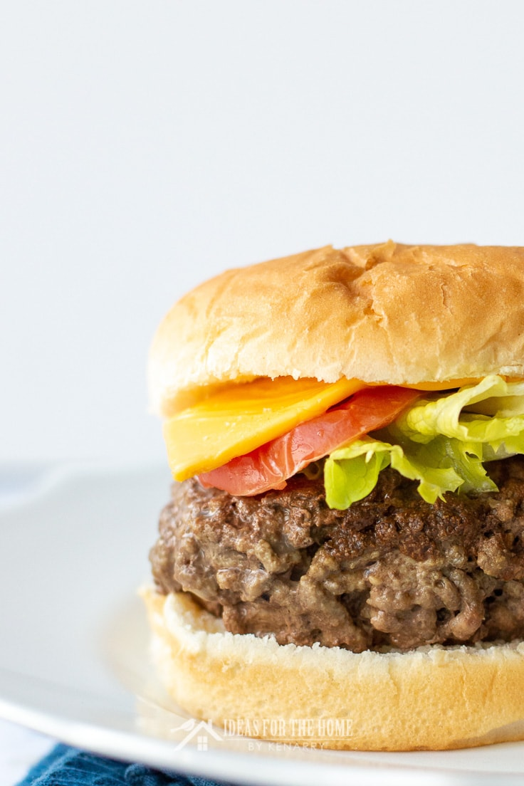 Close up of a meatloaf hamburger on a bun with cheese, tomato and lettuce