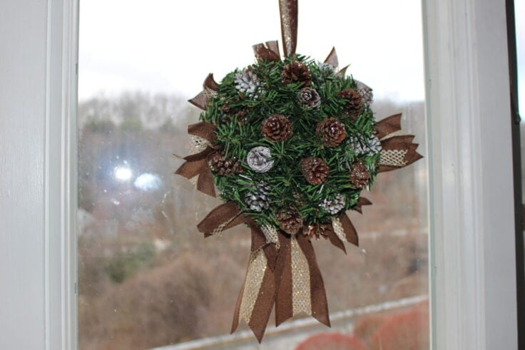 pine cone kissing ball hanging in window