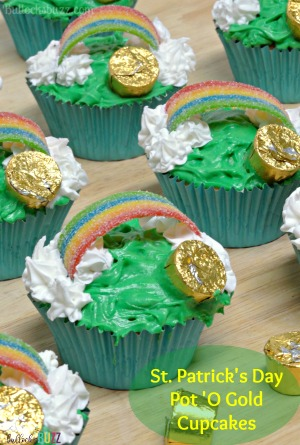 Sweet vanilla cupcakes are decorted with green icing, whipped cream clouds, a candy rainbow and a chocolate pot of gold in these cute St. Patrick's Day Pot of Gold Cupcakes recipe