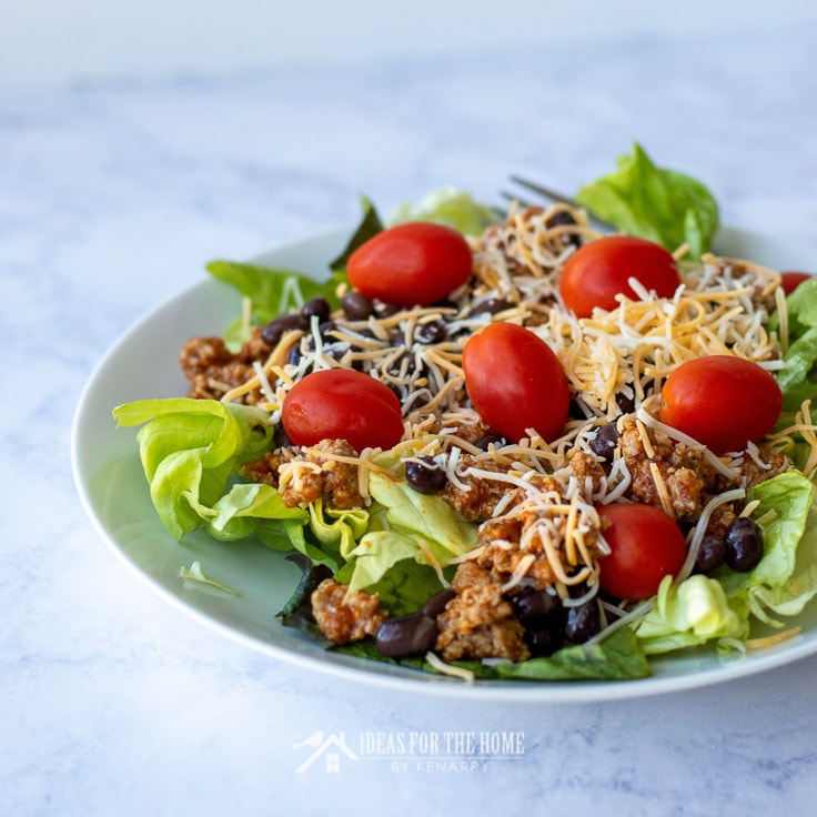 Beef taco salad with crushed nacho chips, black beans, tomatoes, cheese and lettuce