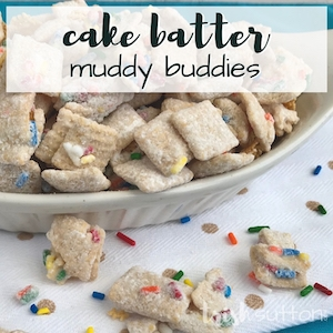 Dish with cake batter muddy buddies on a white surface surrounded by sprinkles.