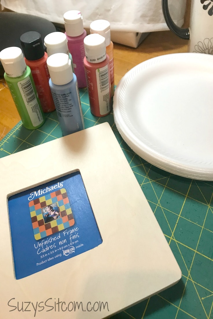 a white picture frame and bottles of acrylic paint