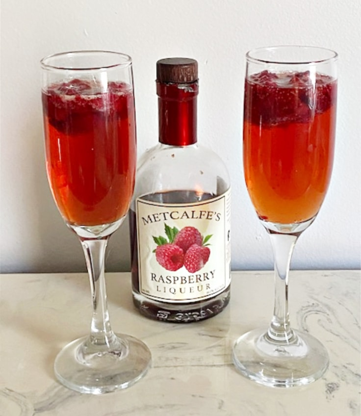 two glasses of raspberry mimosas with raspberry liqueur