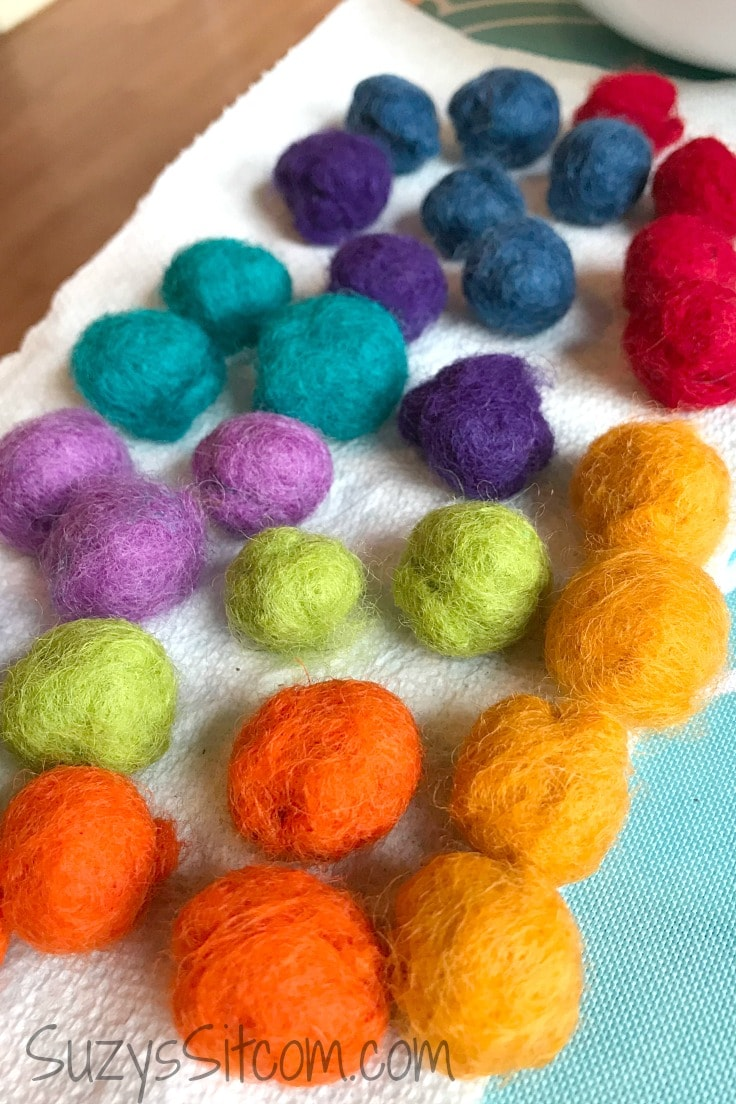 Balls of purple, red, blue, and yellow wool felt