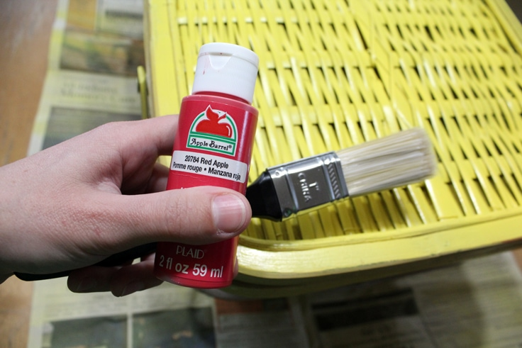 hand holding red craft paint and a brush in front of a yellow picnic basket