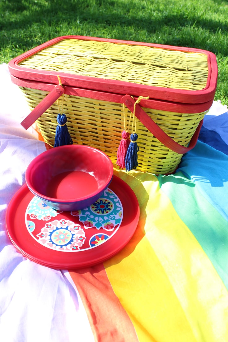 colorful picnic basket and dishes set up on a blanket outdoors