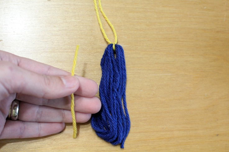 hand holding a tiny piece of yellow yarn beside the blue yarn