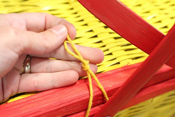 hand tying yarn onto a basket handle