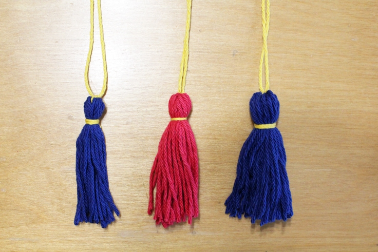 3 tassels - blue, red, and blue - sitting on a table
