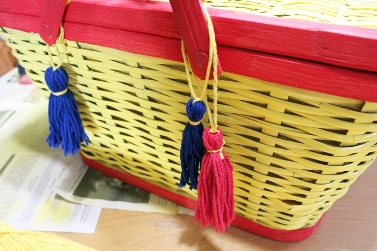 yellow painted picnic basket with red trim decorated with red and blue tassels