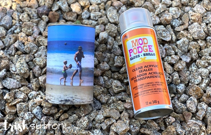 A can of Mod Podge spray laying next to a DIY photo caddy; gravel background.