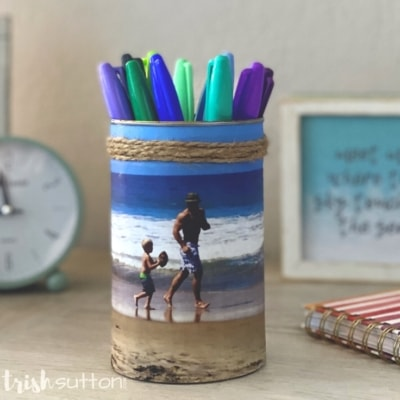 A desk with a DIY photo caddy on it; caddy is filled with colorful sharpies.