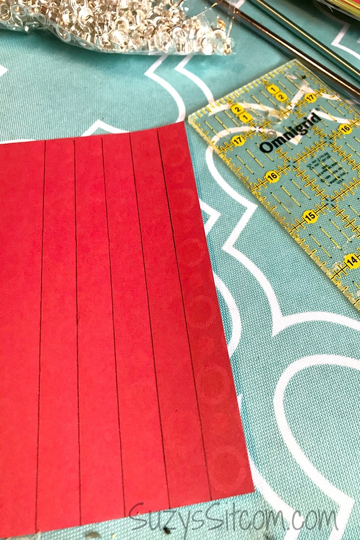 A red sheet of craft paper with vertical lines drawn on it