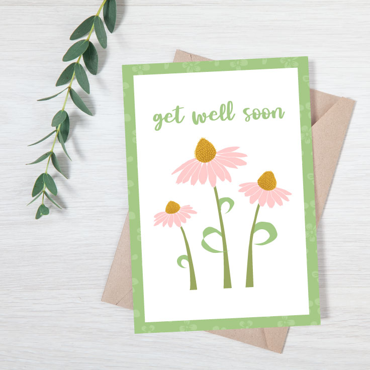 Flower get well soon card on top of envelope with green leaves on top of counter.