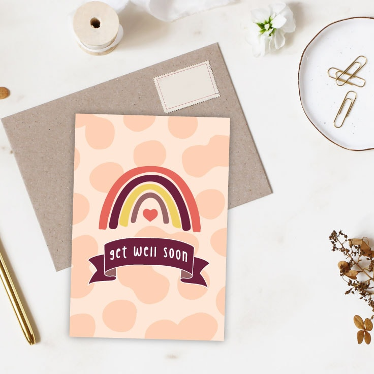 Rainbow get well soon card design on desk with envelope, pen, paperclips and various stationery supplies.