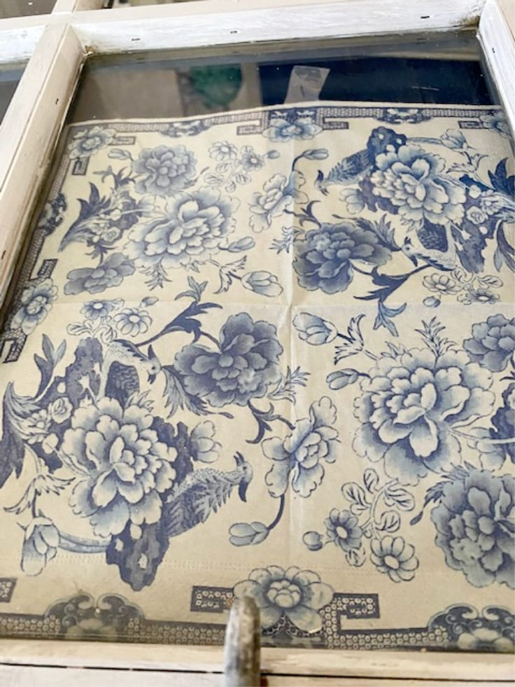 blue and white floral napkin taped to old window