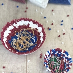 two bead bowls on a wood surface with rubber bands & paperclips in the perler bead bowls