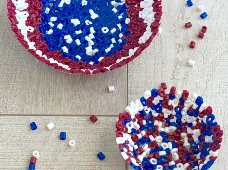two bead bowls on a wood surface with scattered red, white & blue perler beads