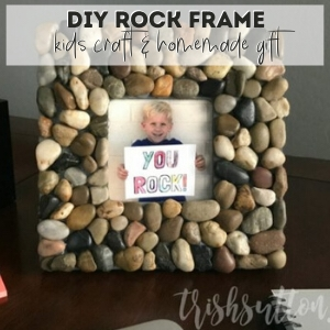 picture frame made out of rocks on a dark surface