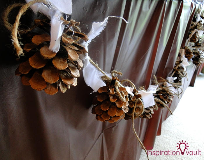 A garland made out of pine cones and white fabric.