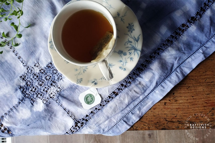 Teacup sitting on a DIY Shibori Tablecloth by Craftivity Designs