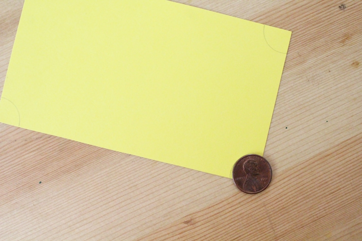yellow paper movie ticket with a penny traced at each corner for the shape