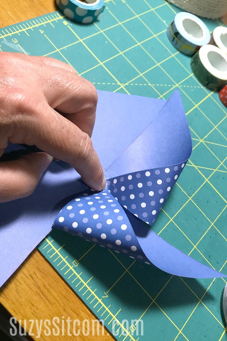 Folding craft paper to make pinwheels